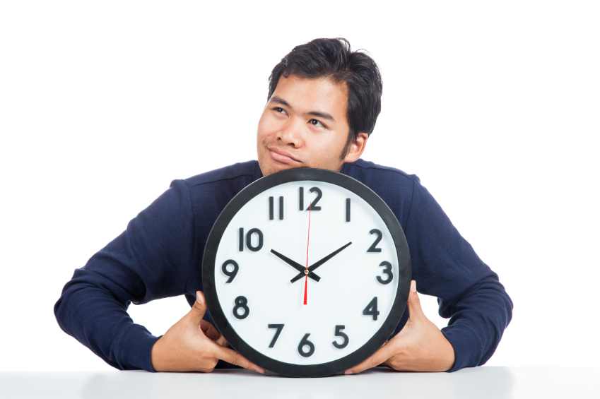 Asian man bored with a clock isolated on white background
