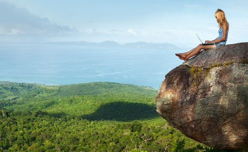Woman on Laptop Sitting on Cliff