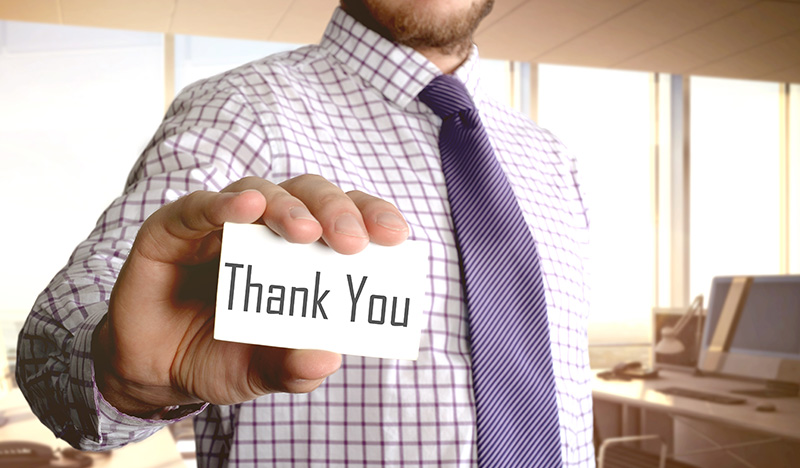 man wearing tie holding thank you card